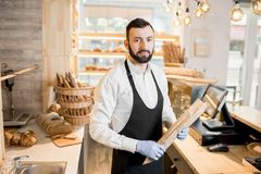 Seller in the bread store. Portrait of a bread seller standing with baguette in the beautiful store with bakery products royalty free stock photos