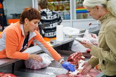 The seller and the buyer in the butcher shop. stock image