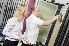 Seller and buyer matching paint color. Assistant seller help choosing paint color and demonstrating matching samples to buyer at hardware store Stock Photos