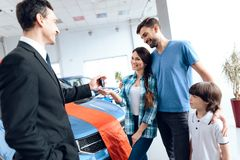 The seller in the car showroom gives the car keys to the buyer. Royalty Free Stock Image