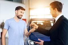 The seller in the car showroom gives the car keys to the buyer. Stock Photos