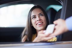 Transfer of keys from the new car. Buying a car in showroom. The seller of cars transfers keys from the new car to the woman. Conceptual image Stock Image