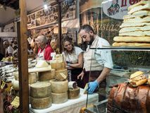 Seller of cheeses and sausages in a street market in the town of. Seller of Grana Padano cheese and cured meats in a street market in the town of Foligno. Umbria royalty free stock image