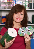 The seller of compact discs. The affable girl - the seller of compact discs near a show-window Stock Image