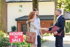 Seller congratulating buying house. Seller congratulating a young couple buying house in suburbs royalty free stock images