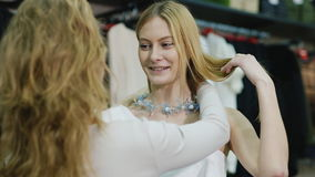 Seller consultant helps shoppers to try on jewelry. The department of women`s clothing and accessories