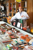 Seller at counter with jamon and wursts Stock Photos
