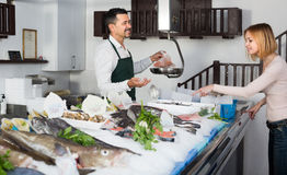 Seller and customer in fish store. Positive smiling seller in apron selling chilled fish to young female in fish store Royalty Free Stock Image