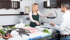 Seller and customer in fishery Royalty Free Stock Images