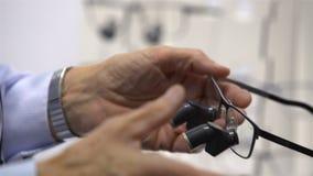 Seller demonstrates new dental loupes lens high resolution. stock video