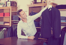 Seller demonstrating cloths. Smiling adult male seller demonstrating cloths in store for man cloths Stock Images