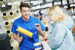 Seller demonstrating paint roller to buyer. Assistant seller help buyer by demonstrating paint roller for painting at hardware store stock photos