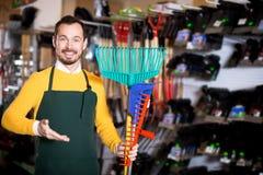 Seller displaying various items in garden equipment shop. Glad man seller displaying various items in garden equipment shop stock image