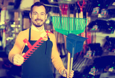 Seller displaying various items in garden equipment shop. Portrait young man seller displaying various items in garden equipment shop royalty free stock photos