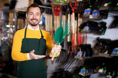 Seller displaying various items in garden equipment shop. Positive young man seller displaying various items in garden equipment shop royalty free stock photography