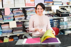 Seller with fabric specimens folder. Portrait of happy woman with fabric specimens folder in textile store Royalty Free Stock Photo