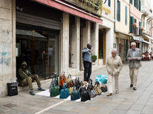 Seller fake branded bags selling bags on the Venetian street Royalty Free Stock Photo
