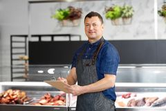 Seller at fish shop writing to clipboard. Food sale, small business and people concept - male seller at fish shop writing to clipboard Royalty Free Stock Photo