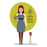 Seller in flower shop holds in hands pot of flower. Royalty Free Stock Photo