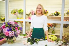 Seller of flowers. Friendly seller of fresh flowers standing by her workplace royalty free stock photos