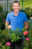 The seller of garden flowers shows roses for choice Royalty Free Stock Images