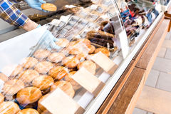 The seller gets a hand pie. home made scones display on a square. under glass showcase. street trading in the market stock photo