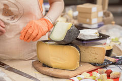 Seller girl sells cheese. Female hands. Cut cheese heads on wooden market board. Selective focus. Seller girl sells the cheese. Female hands. Cut cheese heads Stock Image
