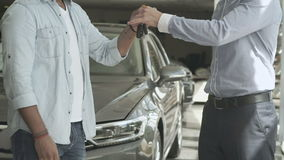 The seller give a keys and shake hands with customer in car showroom. The salesman shakes hands with buyer. The seller gives him a keys from a new car. Two men stock footage