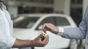 Seller gives a keys to a buyer in car showroom. Close-up. The seller gives the automobile`s keys to the customer. The buyer take a keys in hand. The man just stock video footage