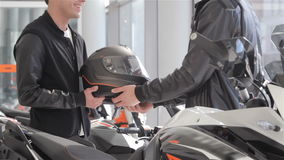 Seller gives motorbike helmet to the buyer. Close up of salesman giving motorcycle helmet to the client. Customer dressed in black jacket and white t-shirt stock video footage