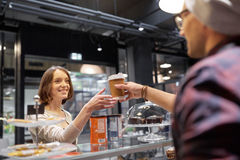Seller giving coffee cup to woman customer at cafe Stock Photo