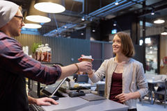 Seller giving coffee cup to woman customer at cafe Stock Images