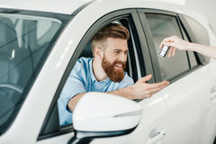 Seller giving key to happy young bearded man Stock Photography