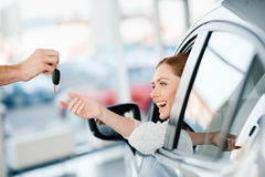 Seller giving key to happy young woman sitting in new car Stock Images