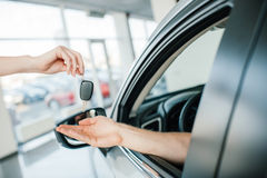 Seller giving key to man sitting in car at showroom Stock Photos
