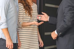 Seller giving keys to buyers. Close-up of seller in black suit giving keys to buyers of flat stock photos