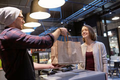 Seller giving paper bag to customer at vegan cafe Royalty Free Stock Images