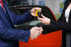 The seller hands over the car keys to the buyer Royalty Free Stock Photos