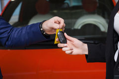 The seller hands over the car keys to the buyer Stock Photos