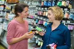 Seller helping client to choose detergents at supermarket Royalty Free Stock Images