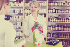 Seller helping customer to choose care products. Mature female seller helping customer to choose care products in specialized shop Stock Images