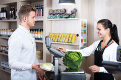 Seller helping customer to weigh cabbage Stock Photo