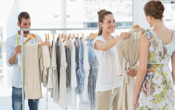 Seller helping shopper choose clothes in store Stock Image