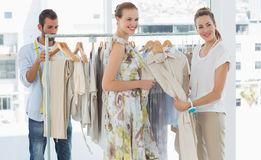 Seller helping shopper choose clothes in store. Female seller helping shopper choose the clothes in the store Royalty Free Stock Photo