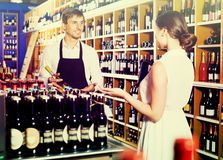 Seller helping to buy bottle. Glad seller men wearing apron helping to buy bottle of wine to women customer in wine store Royalty Free Stock Image