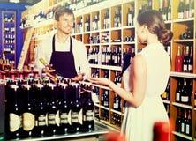 Seller helping to buy bottle. Glad seller men wearing apron helping to buy bottle of wine to women customer in wine store royalty free stock image