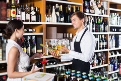 Seller helping to buy bottle. Glad seller wearing apron helping to buy bottle of wine to women customer in wine store stock images