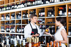 Seller helping to buy bottle. Glad young seller men wearing apron helping to buy bottle of wine to women customer in wine store Stock Photo
