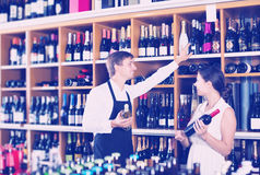 Seller helping to buy bottle. Happy young seller men wearing apron helping to buy bottle of wine to women customer in wine store stock images