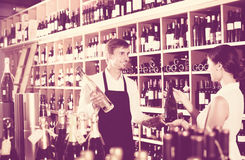 Seller helping to buy bottle. Young seller wearing apron helping to buy bottle of wine to women customer in wine store stock photo